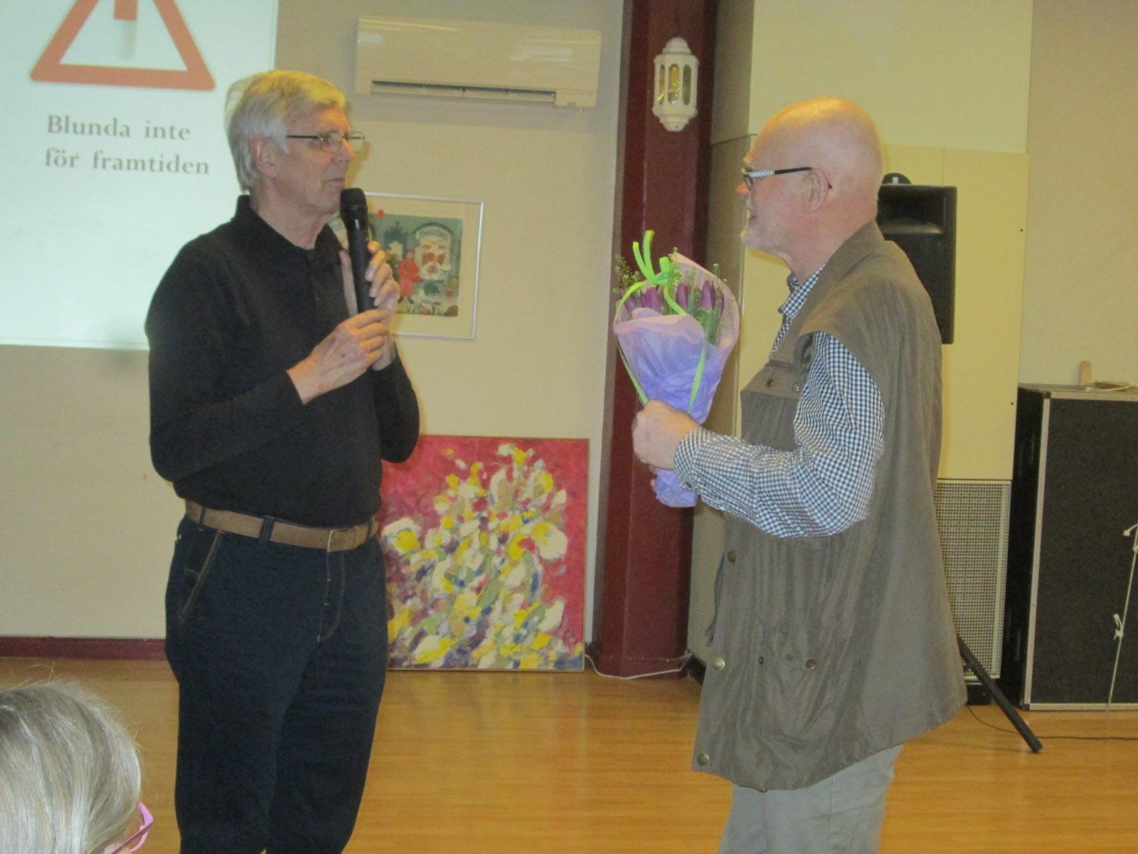 Claes avtackas med en blomma av ordf. Wolfgang