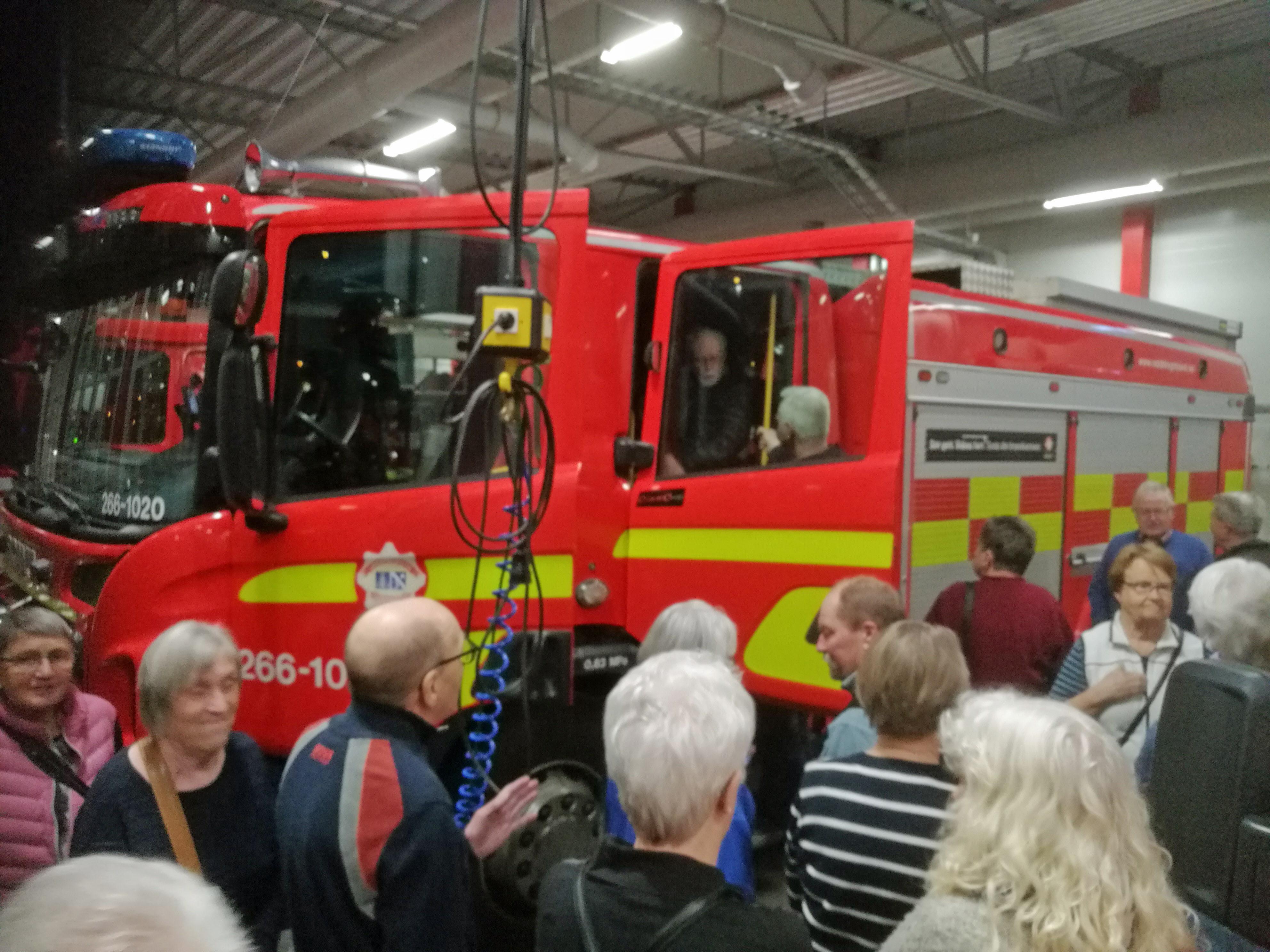 Kent Hoff visar alla finesser på brandbilen för en intresserad publik