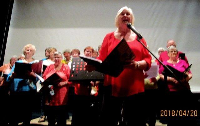 """Vår sångledare Lottie sjunger verserna och kören stämmer in i refrängen på """"Sjung och le""""."""