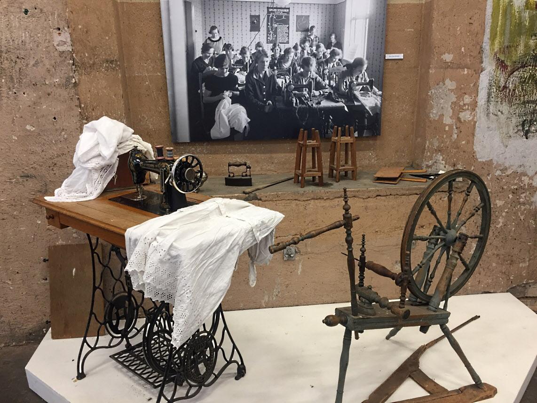 Spinnrock och Husqvarna symaskin. Kvinnorna fick gå kurser för att lära sig sy på maskin.