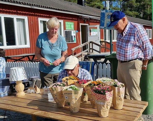 Erik graverar priser. Sonja och Kjell  kollar så det blir rätt.