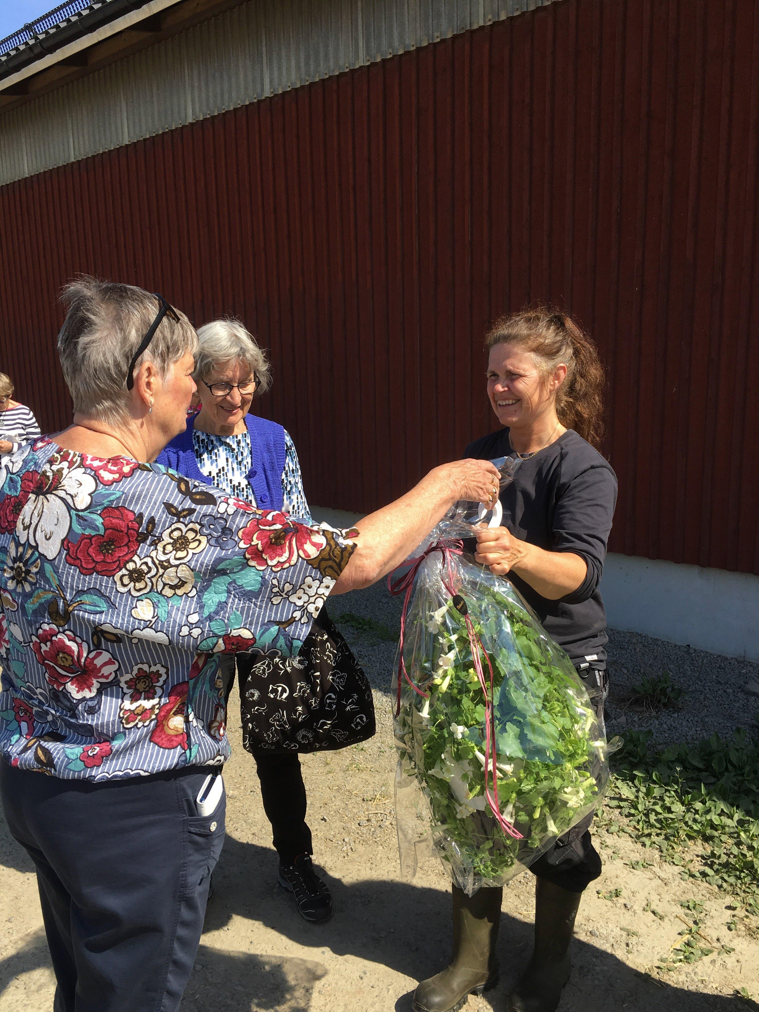 Ordförande Maud Kvarnäng tackar Kristina Mickelsson med en blomma efter besöket på Vallens gård