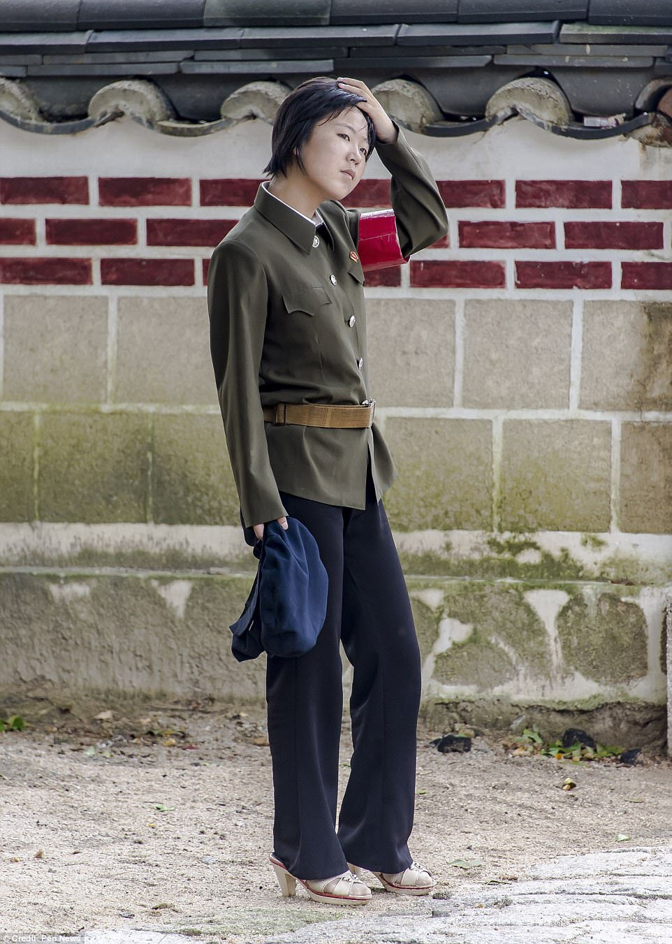 One photo shows a female soldier in military clothing on duty in high heels. The image was among a number smuggled out of the secretive country
