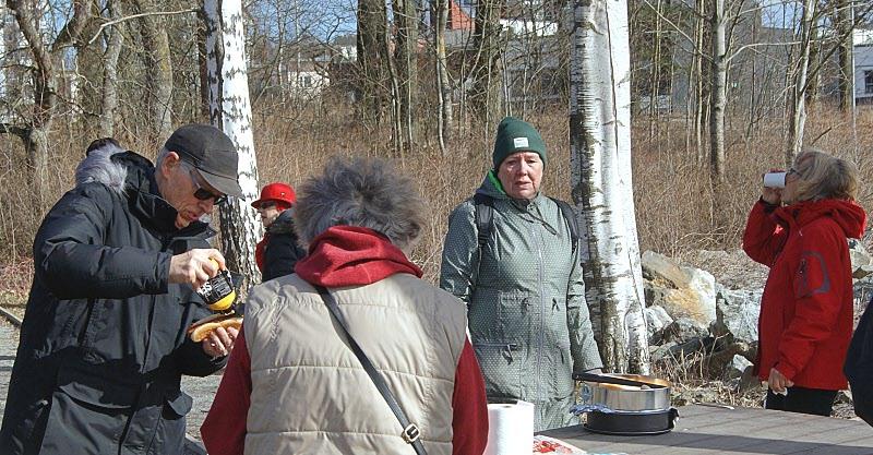 Här kollar Pirkko avståndet mellan deltagarna eller kanske väntar på att få servera mer korv.